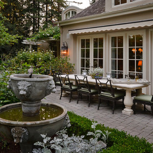 Design ideas for a mediterranean back patio in San Francisco with a water feature and an awning.