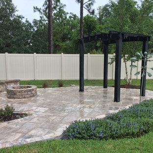 Foto di un patio o portico chic di medie dimensioni e dietro casa con un focolare, cemento stampato e una pergola