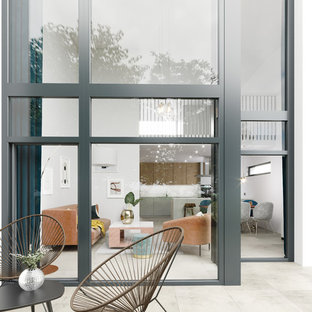 Photo of a contemporary back patio in London with tiled flooring.