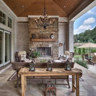 Esempio di un grande patio o portico stile rurale dietro casa con un tetto a sbalzo, pavimentazioni in pietra naturale e un caminetto