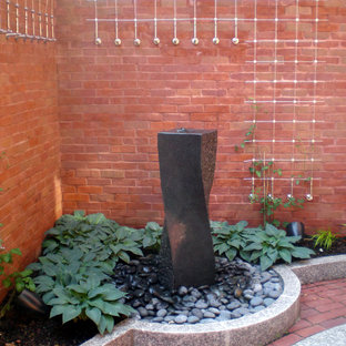 Photo of a small contemporary courtyard patio in Boston with a water feature and brick pavers.