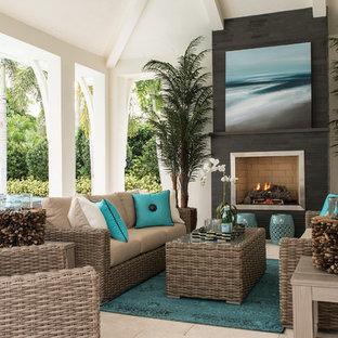 Immagine di un grande patio o portico stile marino dietro casa con piastrelle, un tetto a sbalzo e un caminetto