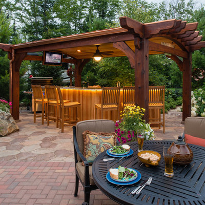 Example of a mid-sized classic backyard brick patio design in Other with a gazebo