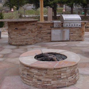 Mid-sized southwest backyard stone patio kitchen photo in Albuquerque with a pergola