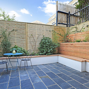 Inspiration for a medium sized contemporary back patio in London with natural stone paving.