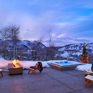 Aménagement d'une grande terrasse arrière contemporaine avec un foyer extérieur, des pavés en béton et aucune couverture.