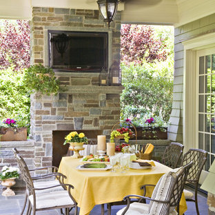 Example of a mid-sized classic backyard tile patio design in New York with a fire pit and a roof extension