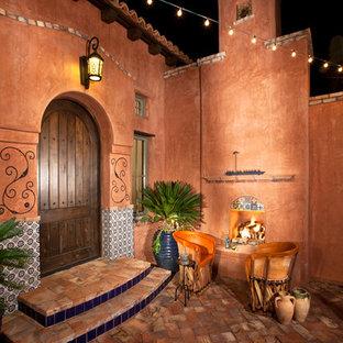 Réalisation d'une terrasse sud-ouest américain avec un foyer extérieur, une cour, des pavés en brique et aucune couverture.
