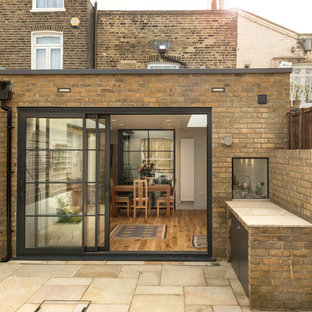 Inspiration for a small contemporary back patio in London with an outdoor kitchen and natural stone paving.