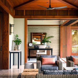 Esempio di un grande patio o portico tropicale dietro casa con piastrelle e un tetto a sbalzo