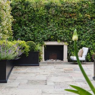 Exempel på en klassisk gårdsplan, med en vertikal trädgård och naturstensplattor