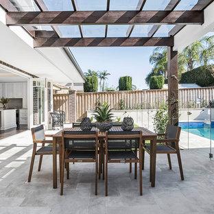 Modelo de patio tradicional renovado, de tamaño medio, en patio trasero, con adoquines de piedra natural, jardín de macetas y pérgola