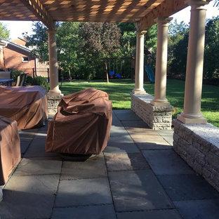 Foto di un grande patio o portico chic dietro casa con pavimentazioni in pietra naturale e una pergola