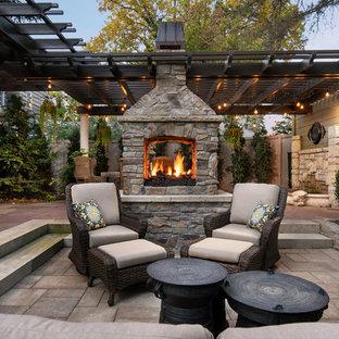 Foto di un patio o portico vittoriano di medie dimensioni e dietro casa con un focolare, pavimentazioni in cemento e una pergola
