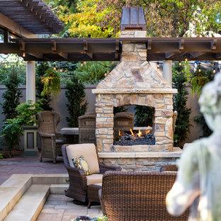 Esempio di un patio o portico vittoriano di medie dimensioni e dietro casa con un focolare, pavimentazioni in cemento e una pergola