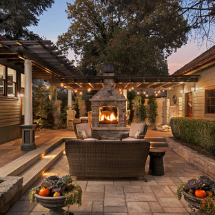 This is an example of a mid-sized victorian backyard patio in Boise with a fire feature, natural stone pavers and a pergola.