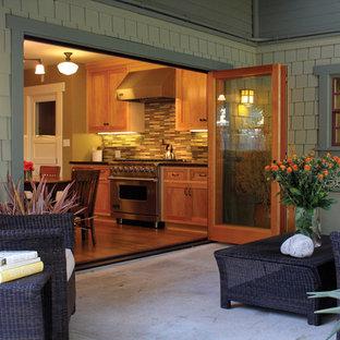 Aménagement d'une grande terrasse arrière craftsman avec une extension de toiture et une dalle de béton.