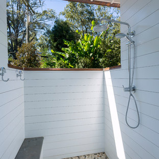 Photo of a beach style patio in Charlotte with an outdoor shower, tile and a roof extension.