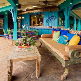 Immagine di un grande patio o portico tropicale dietro casa con un tetto a sbalzo e piastrelle