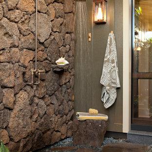 Immagine di un ampio patio o portico tropicale nel cortile laterale con pavimentazioni in pietra naturale e nessuna copertura