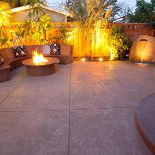 Idee per un patio o portico tropicale di medie dimensioni e dietro casa con un focolare, cemento stampato e nessuna copertura