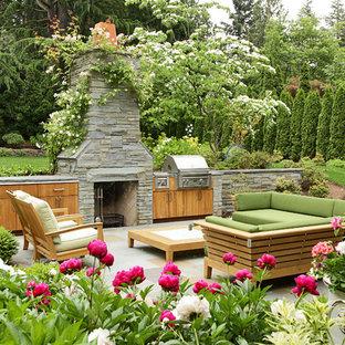 Esempio di un patio o portico chic dietro casa con pavimentazioni in pietra naturale, nessuna copertura e un caminetto