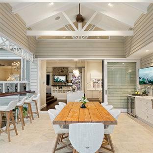 Immagine di un grande patio o portico stile marino con piastrelle e un tetto a sbalzo
