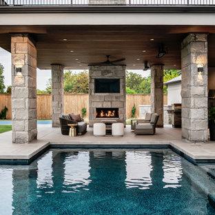 Ispirazione per un patio o portico minimal dietro casa con un caminetto, lastre di cemento e un tetto a sbalzo