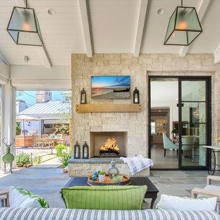 Immagine di un grande patio o portico costiero dietro casa con un focolare, pavimentazioni in pietra naturale e un tetto a sbalzo