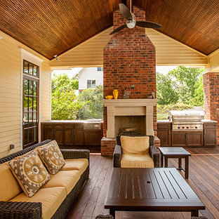 Example of a mid-sized ornate backyard patio kitchen design in Houston with decking and a roof extension