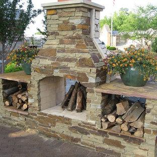 Ispirazione per un patio o portico tradizionale nel cortile laterale con un caminetto, pavimentazioni in mattoni e nessuna copertura