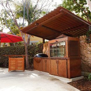 Immagine di un patio o portico industriale di medie dimensioni e dietro casa con lastre di cemento e un parasole