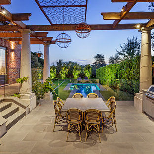 This is an example of a large transitional patio in Melbourne with an outdoor kitchen, tile and a pergola.