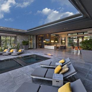 Esempio di un ampio patio o portico minimalista dietro casa con un focolare, pavimentazioni in pietra naturale e un tetto a sbalzo