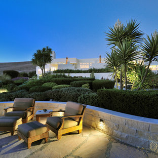 Large contemporary backyard patio in Other with natural stone pavers and no cover.