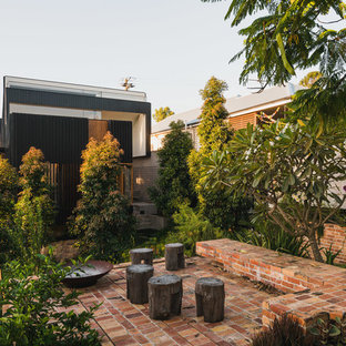 Inspiration for a contemporary backyard patio in Brisbane with brick pavers and a fire feature.