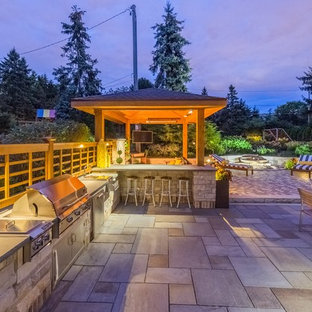 Inspiration for a large traditional backyard patio in Milwaukee with an outdoor kitchen, a gazebo/cabana and natural stone pavers.