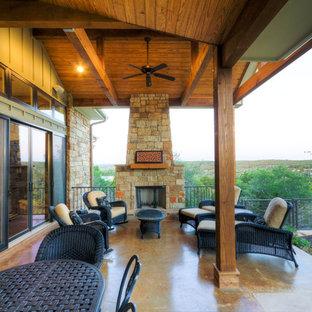 Esempio di un patio o portico american style di medie dimensioni e dietro casa con un caminetto, lastre di cemento e un parasole