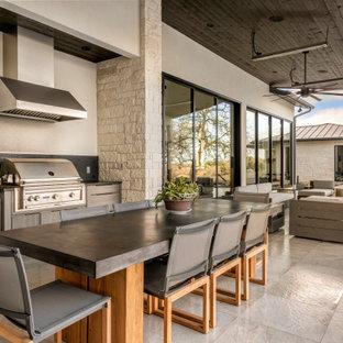 Cette photo montre une terrasse avec une cuisine extérieure tendance avec du carrelage et une extension de toiture.