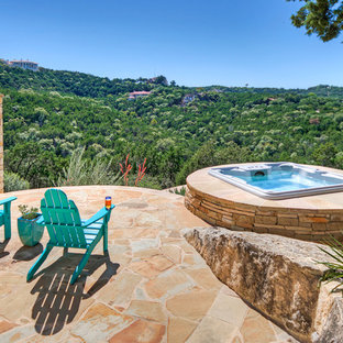 Example of a mountain style stone patio design in Austin
