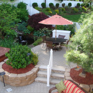 This is an example of a large classic back patio in New York with brick paving and an awning.