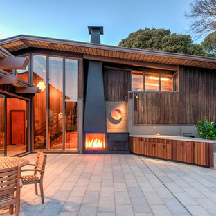 Photo of a large midcentury backyard patio in San Francisco with no cover, with fireplace and concrete pavers.