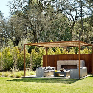 Inspiration for a mid-sized contemporary backyard patio in Boston with a pergola and with fireplace.