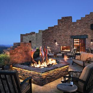 Idée de décoration pour une très grande terrasse arrière sud-ouest américain avec un foyer extérieur, aucune couverture et du carrelage.