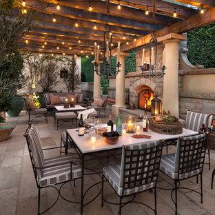 Esempio di un patio o portico mediterraneo con una pergola