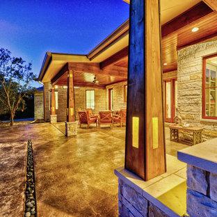 Foto di un grande patio o portico bohémian dietro casa con fontane, cemento stampato e un tetto a sbalzo