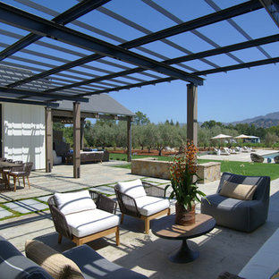 Example of a country backyard concrete paver patio design in San Francisco with a pergola