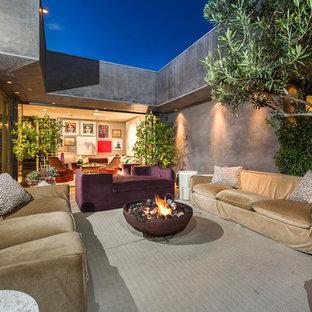 Foto di un grande patio o portico bohémian dietro casa con un focolare, nessuna copertura e lastre di cemento