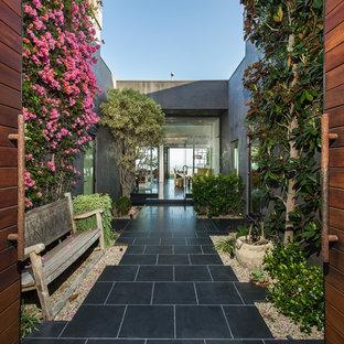 Immagine di un grande patio o portico bohémian davanti casa con pavimentazioni in pietra naturale e nessuna copertura