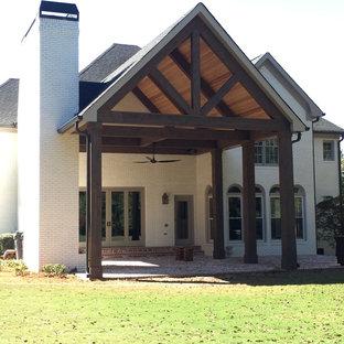 Esempio di un grande patio o portico classico dietro casa con un focolare, pavimentazioni in mattoni e un tetto a sbalzo